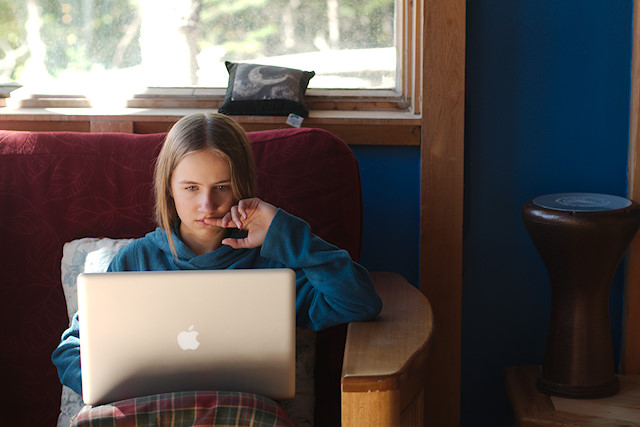 teen girl on couch with computer