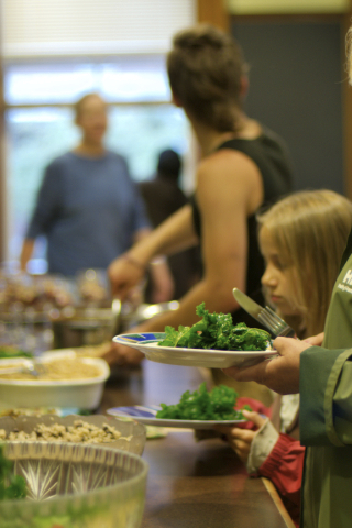 Eating raw young kale: at a community fundraising supper